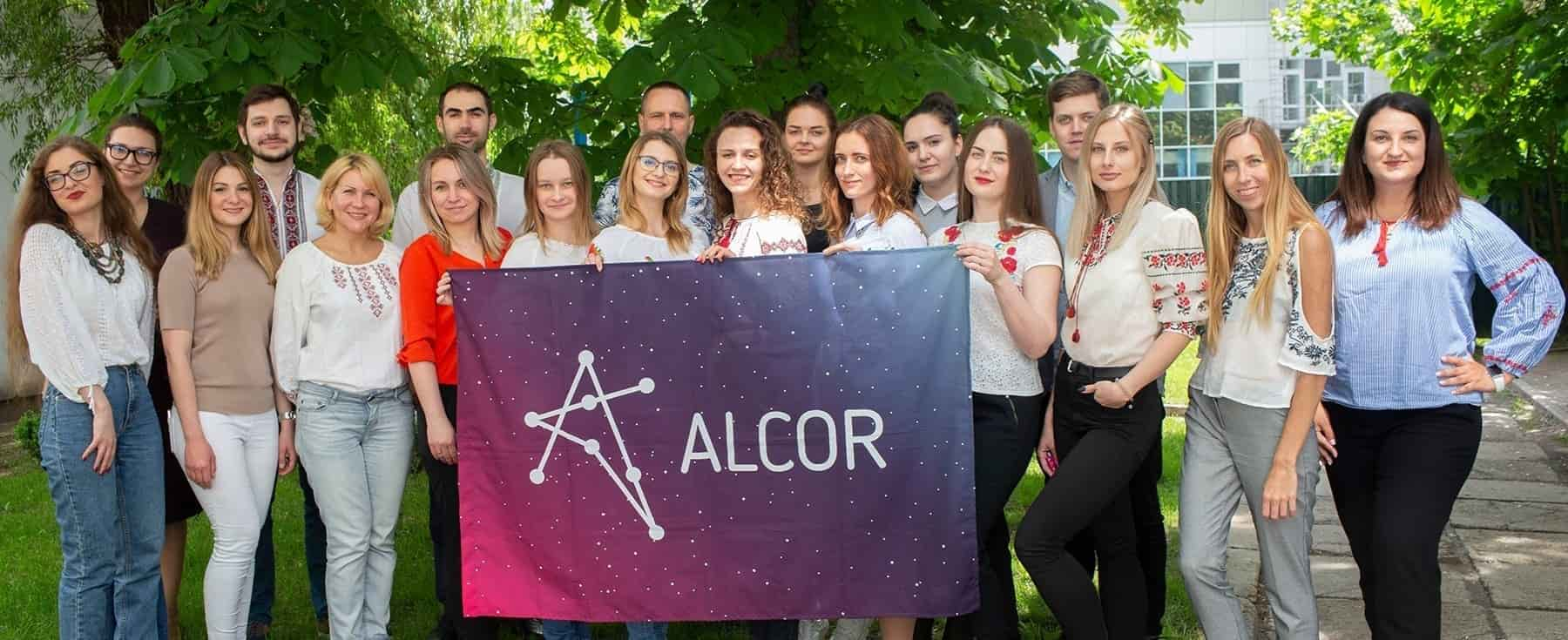 Alcor employees with a flag